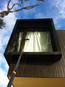 Shows waterfed pole cleaning inaccessible house window